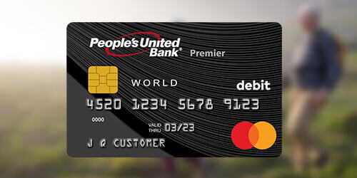 People's United Bank black World Debit Mastercard® Debit Card laying on a blurred background of a couple hiking.