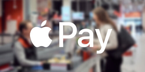 White ApplePay logo on top of a blurred background image showing a customer at a retail checkout counter