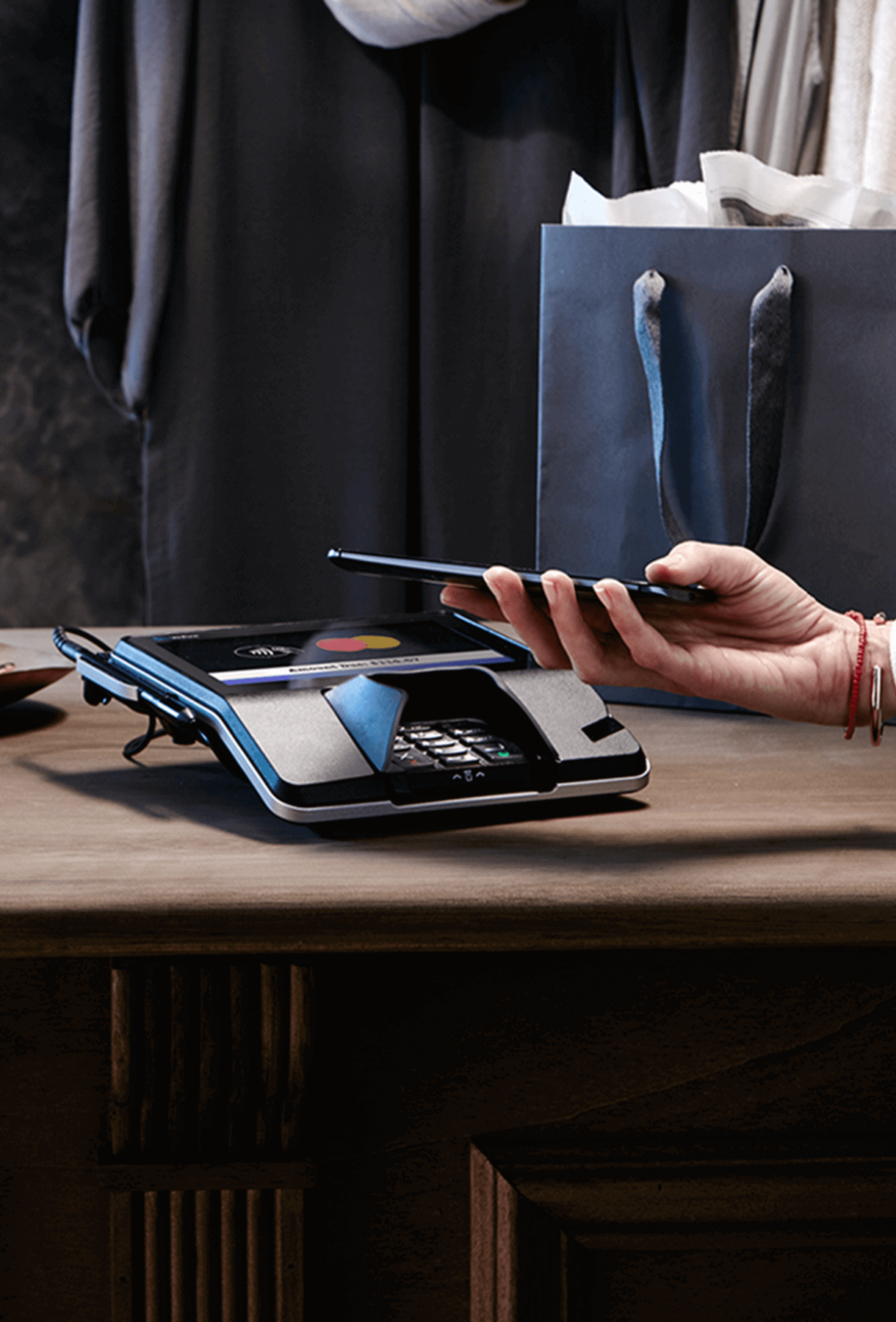 Hand holding mobile phone above card reader to make a purchase at a retail clothing store