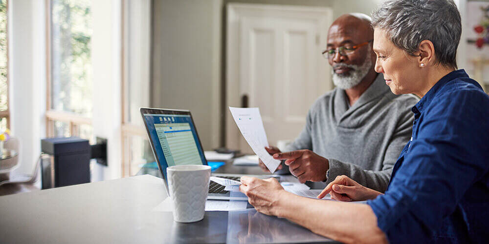 A mature couple sitting side-by-side at home reviewing benefits forms together in front of an open laptop