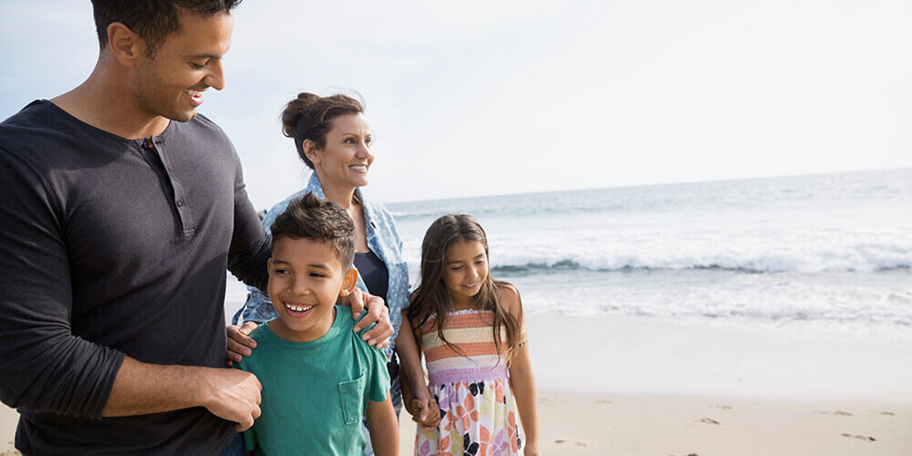 Father smiles down at son with arm on shoulder while mother holds daughter's hand and the family enjoys a walk on the beach