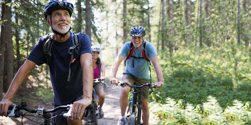 Mature, fit man with beard and backpack bikes through a forest path with a man and woman on a sunny day enjoying the scenery