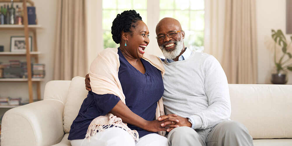 A retired couple sit on the couch in their home and laugh