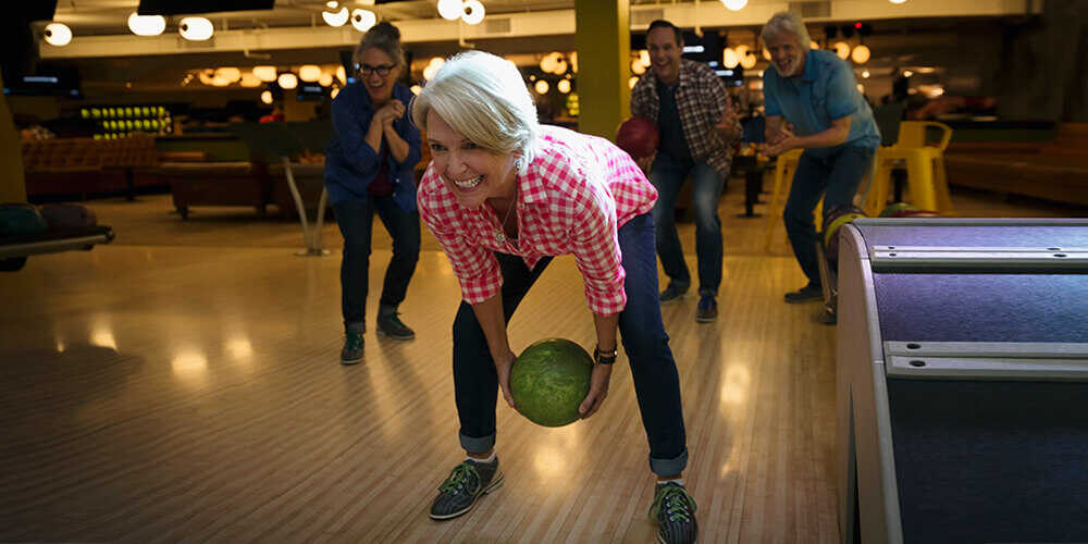 A mature woman with white hair and a pink checkered shirt, smiles as she gets ready to throw a green bowling ball while her friends cheer in the background.