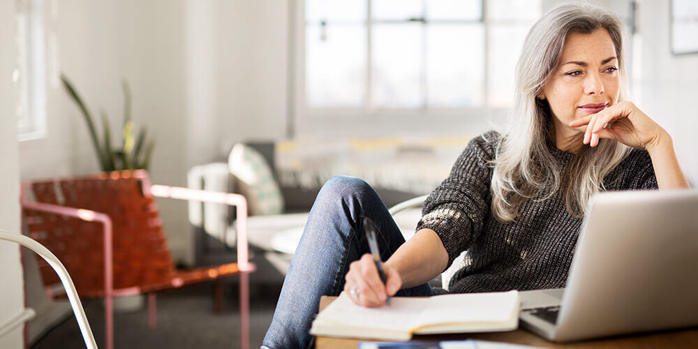 A woman with long gray hair stares into the distance, thinking about what to write in her notebook, with a laptop also in front of her.