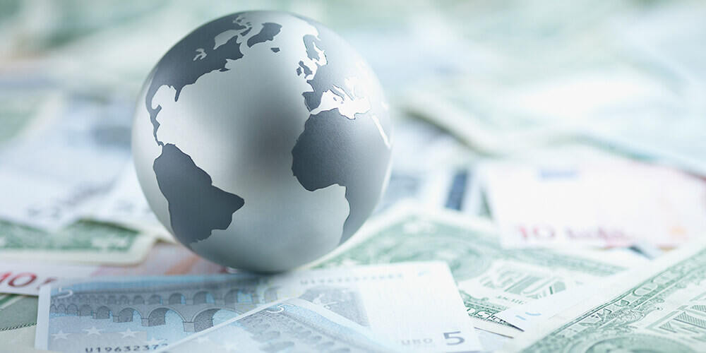 A silver globe of the Earth sits on a pile of paper currency from around the world