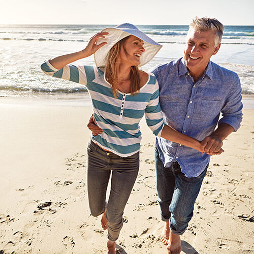 Woman holding white floppy hat holds hands with man as they run on a sandy beach with the water and waves in the background