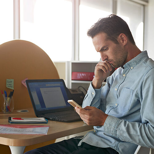 Man wearing light blue button-down shirt, sitting at desk with laptop and seeming concerned while looking at mobile phone.