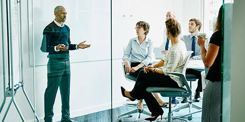 A business man stands at a whiteboard in a glass conference room and presents to his colleagues.