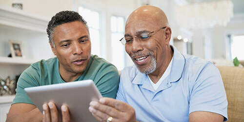 A father in a light blue polo shirt and glasses sits with his adult son in a green tshirt as they happily look at a tablet.