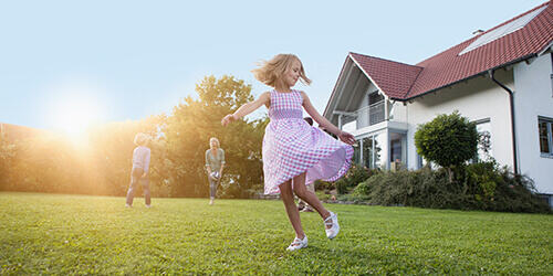 A young girl in a pink dress dances and twirls in her backyard while her family plays in the background.