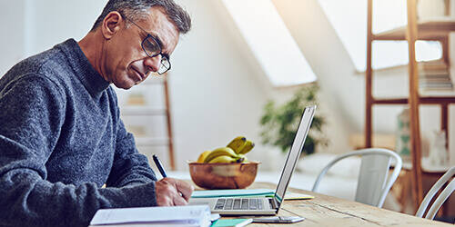 Mature man in gray sweater writes in appointment book with his laptop open on the desk and a bowl of bananas in the background