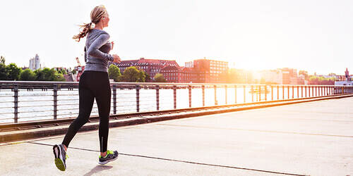 A woman with a blonde ponytail jogs on the sidewalk along a river in a city, heading  toward the sunrise.