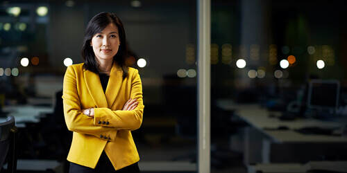 Confident, professional wealth advisor stands alone with her arms crossed in a bright yellow jacket in a dark office