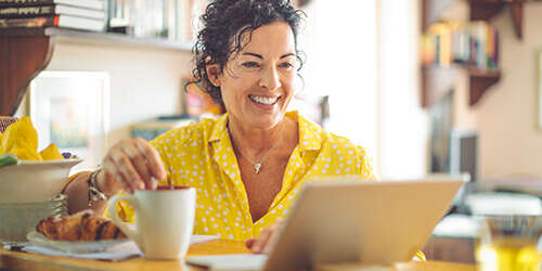 Mature woman in a bright yellow shirt enjoys coffee and a croissant at the kitchen counter while banking online