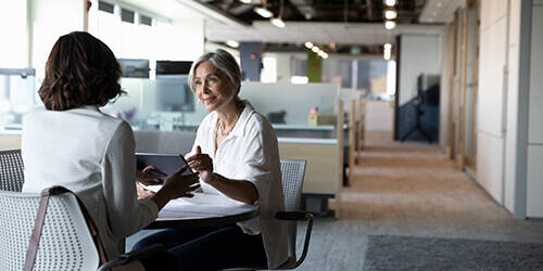 A mature woman with white hair and a white shirt meets with another woman in an open, empty office.