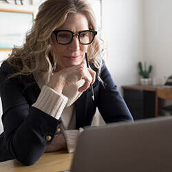 Mature woman in glasses rests her chin on hand sits at desk focused on her laptop reading a how-to-guide on online banking